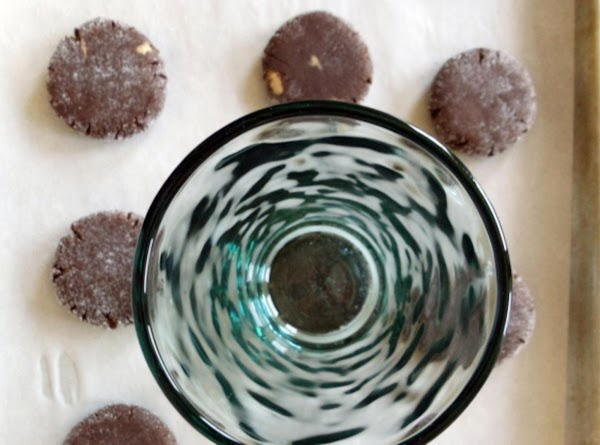 Grease the bottom of a drinking glass, and use it to flatten each cookie...