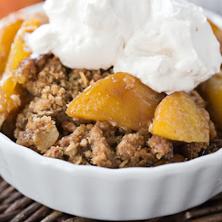 Warm Vanilla-Bourbon Peach Crisp with Pecans, topped with Whipped Vanilla Cream