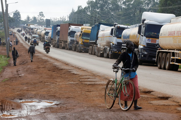 Woman walks past trucks waiting in a queue to cross the Kenyan-Ugandan border in the town of Busia, Kenya, November 14 2020. Picture: REUTERS/BAZ RATNER
