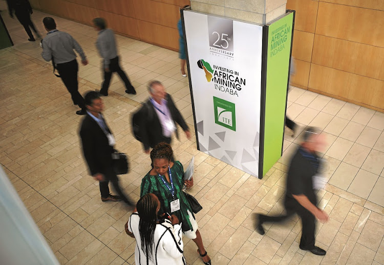Delegates walk past billboards at the Investing in African 2019 Mining Indaba. There was a notable feeling of cheeriness conference in Cape Town. Picture: Reuters/Mike Hutchings