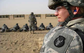 Photo: Staff Sgt. Julie Mason, a medic with the 34th Red Bull infantry Division, waits to fire her weapon while other Red Bull Soldiers check their weapon's sight on a firing range outside of Camp Buehring, Kuwait.