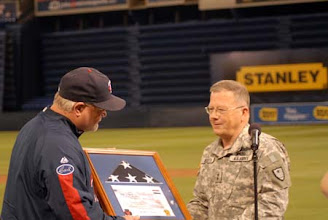 Photo: Maj. Gen. Larry Shellito presents the flag to Twins Manager Ron Gardenhire.