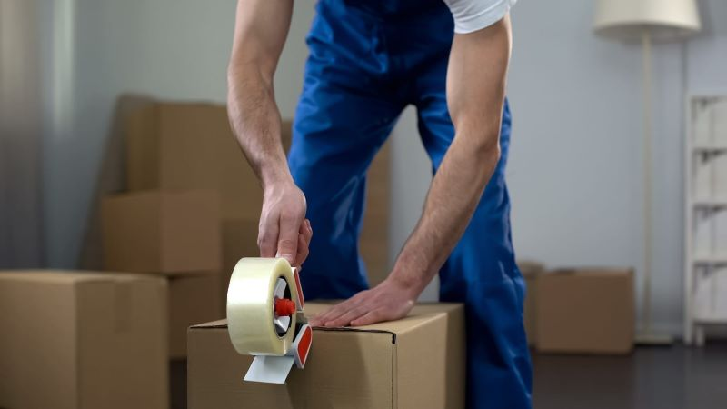 Professional mover packing a box