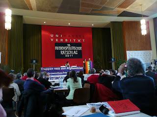 Saal mit Kongressteilnehmern, Podium, dahinter Transparent: »Universität Kassel Friedensratlschlag«.