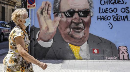 Una mujer camina frente a un grafiti de Juan Carlos I dibujado en Valencia.