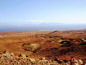 Photo: View looking back down barren landscape to Porto Novo. View of Island of Sao Vicente in the far distance.