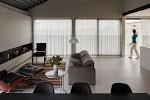 vrouw schuift vitrage dicht in gezellige, moderne, woonkamer