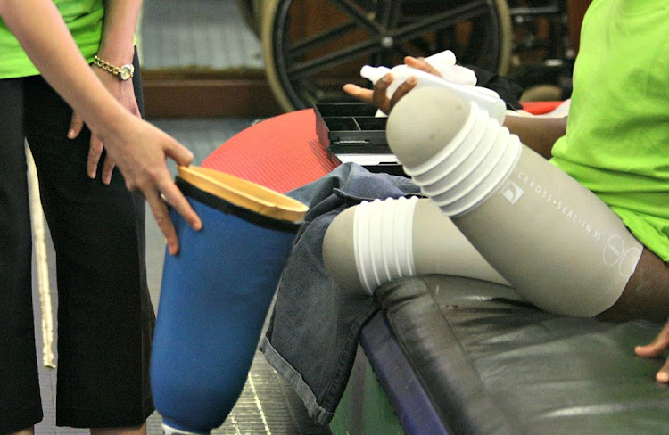 An occupational therapist helps a young double amputee fit his legs during rehabilitation. File photo: SOWETAN/VATHISWA RUSELO.