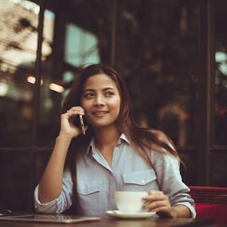a woman on the phone at a coffee shop while having a cup of coffee