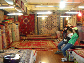 Photo: This is a horribly focused picture, but the only one I have of a carpet vendor... Oriental carpets are everywhere in Urumqi! Some are silk, some wool, some nylon...