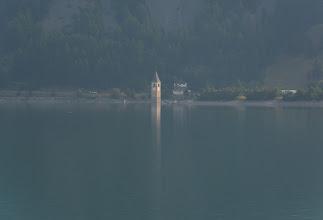 Photo: Romańska dzwonnica dawnego kościoła parafialnego św. Katarzyny to jedyne co pozostało ze starego Graun. W 1950 roku miejscowość została zrównana z ziemią i zalana wodami powstającego jeziora.