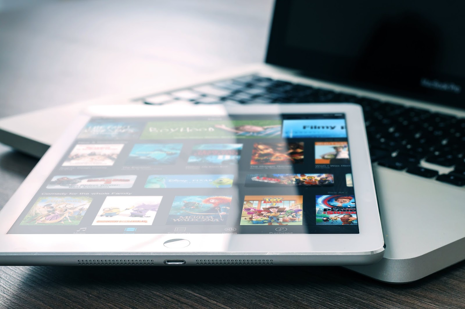 iPad showing a movie streaming service with a Macbook in the background.