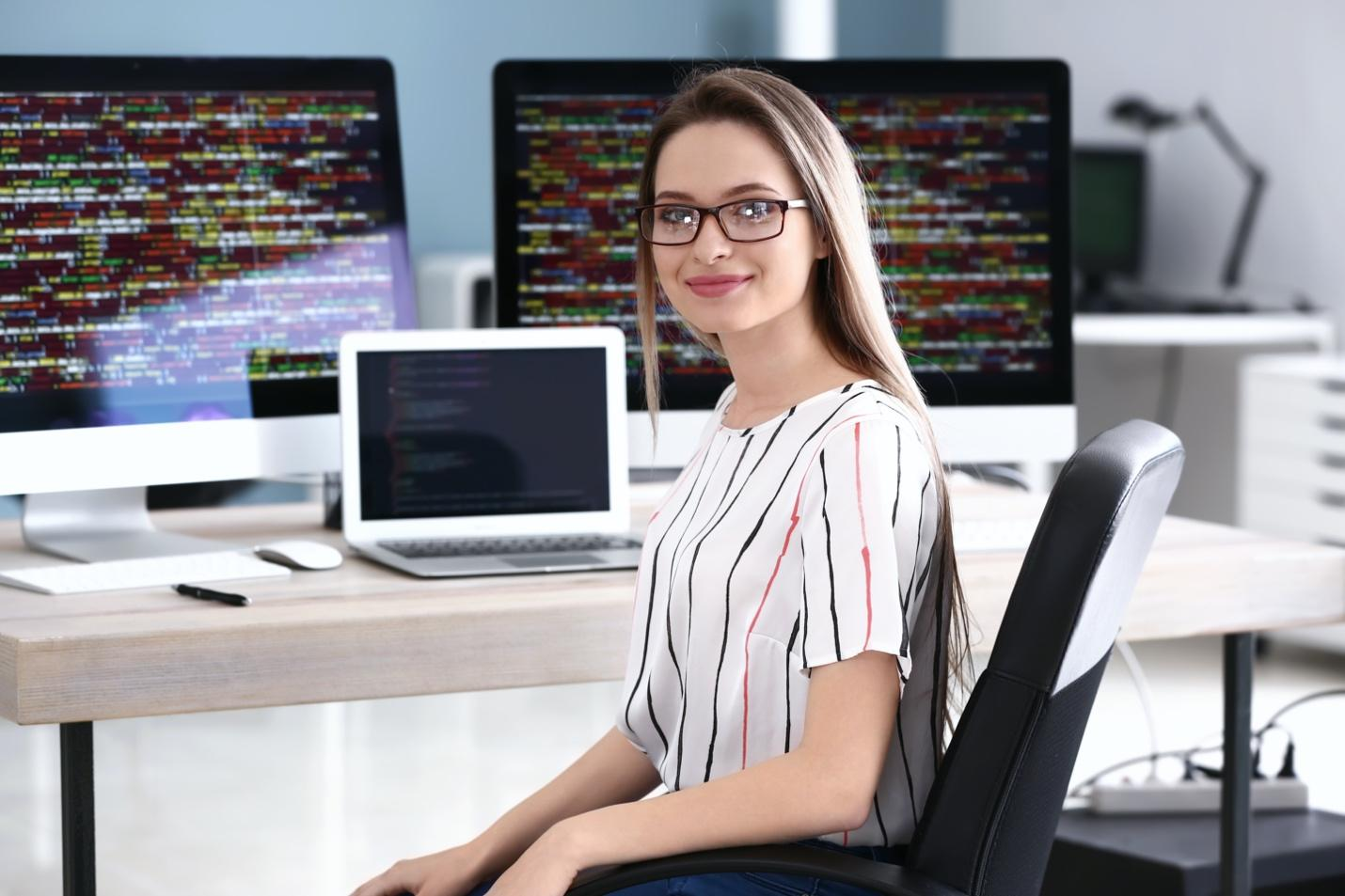 Woman smiling after getting her first job in tech sector.