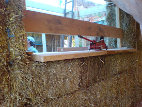Photo: compression of bales under window via jacks wedged between temp timber and sill