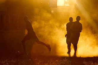 Photo: Schoolboys playing a dusty game of football in the setting sun. Port-Bergé, Madagascar.