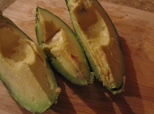 I found the best way to skewer avocados is to first slice the avocado in half and remove he pit.  Slice them with the skin on in equal slices lengthwise, then peel off the skin.