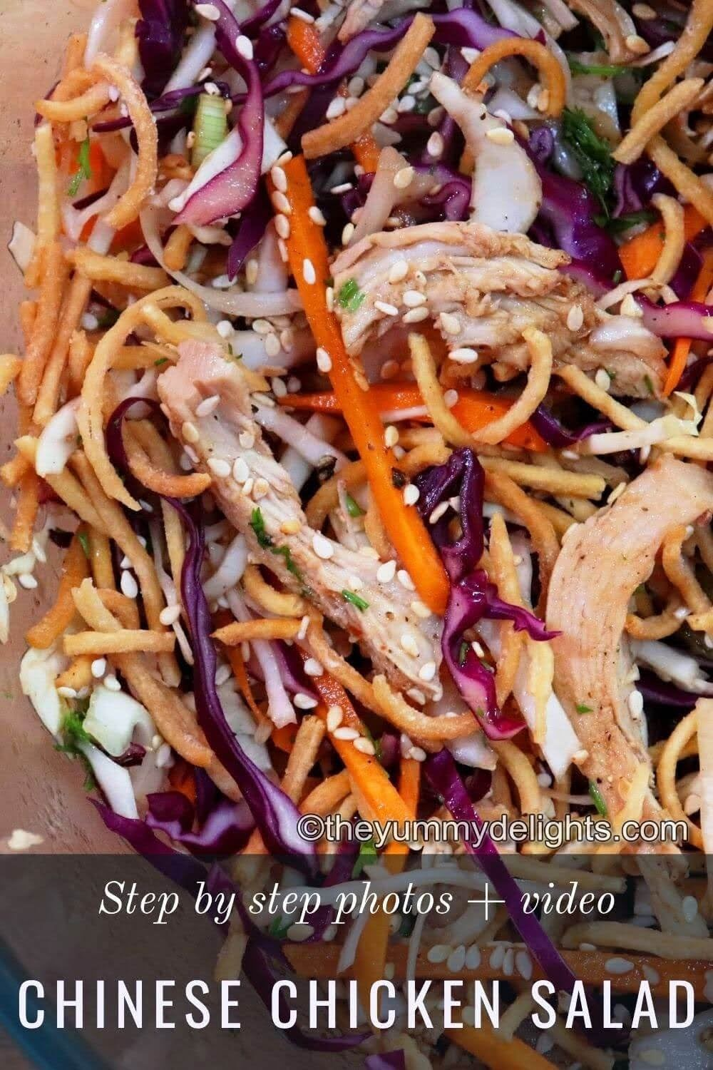 close view of chinese chicken salad with Asian dressing. Garnished with roastes sesame seeds and fried noodles.