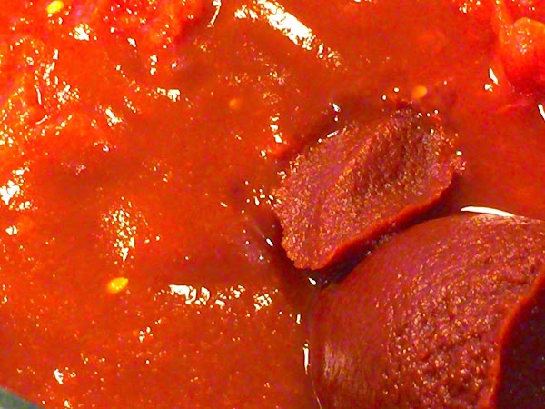 To the tomatoes in the mixing bowl, add tomato sauce and tomato paste; mixing...