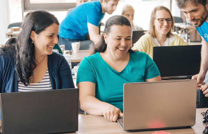 Three people smiling while looking at a laptop
