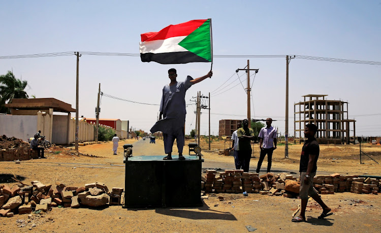A Sudanese protester holds a national flag in Khartoum, Sudan. Picture: REUTERS