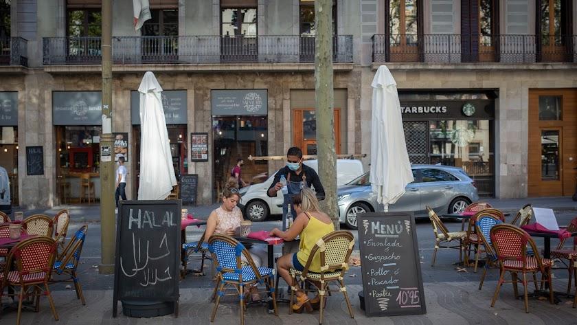 Dos mujeres comen en la terraza de un bar en Barcelona.