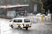 People take cover  from the heavy rain at the Rea Vaya bus station in Johanessburg. / KABELO MOKOENA