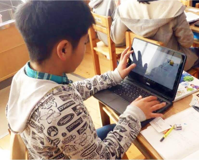 Chromebook を机で使う子供