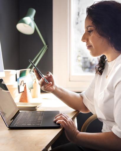 Una donna è seduta alla scrivania e sta usando il suo telefono.