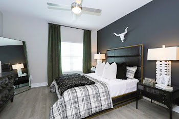 Bedroom with navy accent wall, bed, night stands, and full length mirror in corner
