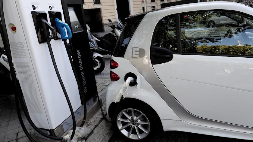 Imagen de un vehículo híbrido mientras procede a cargarse en un punto de recarga de batería.