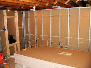 Photo: Looking at left side of screen wall. Equipment rack cutout on the left. Recess lighting can be seen in between ceiling joists.