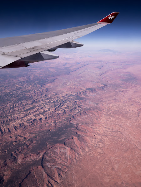 Photo: Grand Canyon (probably)  I love flights to and from Las Vegas: beyond an aerial view of The Strip, there's a good chance you'll also catch a glimpse of the Hoover Dam or a Canyon or three. Here's one (apparently) of The Grand Canyon which I took towards the end of my Virgin Atlantic flight from London Gatwick to Las Vegas a few days ago.  Just before the seatbelt signs came on, the pilot announced anyone on the right side of the plane would enjoy a good view of the Grand Canyon. Cue pretty much every passenger leaping out of their seat and crowding around the windows until I'm sure the plane was forced to go round in circles.  Anyway, once I got a clear view of the window, this was my view. I'm not sure if it's still the Grand Canyon or not, but I'm pleased with it. As always I used my Panasonic GX1, this time fitted with the Lumix 7-14mm at 14mm, or 28mm equivalent. When shooting through a window, I always find pushing the lens right up against it will minimize reflections, and cupping any gaps with your hands should get rid of any other unwanted light from inside the cabin or room. Lens hoods are perfect for doing this as they allow you to essentially make a light seal with a window, without actually touching it with your precious optics. I also find shooting with daylight white balance and nudging the exposure compensation down a little helps. Either way, you'll almost certainly be tweaking the levels a bit afterwards to bring back some blacks and boost the contrast. That's pretty much all I've done here.  I'm especially excited to post this image tonight as I'm currently about two hour's drive from the Canyon and will be visiting tomorrow! It's been about ten years since I was last there and my digital camera back then had just two Megapixels!