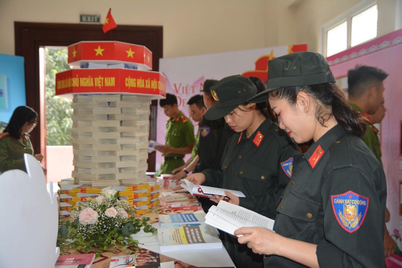 Nữ cảnh sát đặc nhiệm Công an Nghệ An chăm chú tìm hiểu những đầu sách được trưng bày