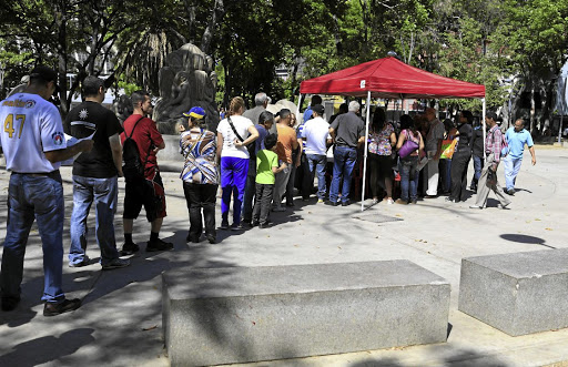Checking: Venezuelan citizens wait to check in at a 'red point' set up by President Nicolas Maduro's party, to verify they voted during the presidential election in Caracas, Venezuela, on Sunday. Picture: REUTERS