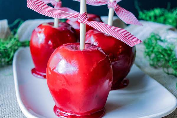 Three Cinnamon Candy Apples On A White Plate.