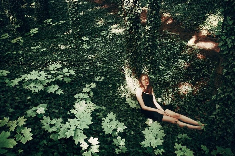 Photo d'une femme assise contre un arbre, entourée de verdure