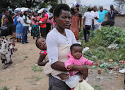 Nonhlanhla Ncube with her children, three-month-old Simphiwe (front) and Thando Moyo (3) at a centre where they received assistance with basic needs.