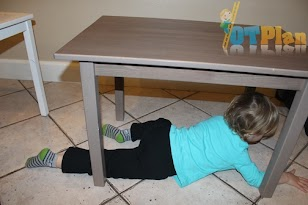 """""""The child is under the table."""""""