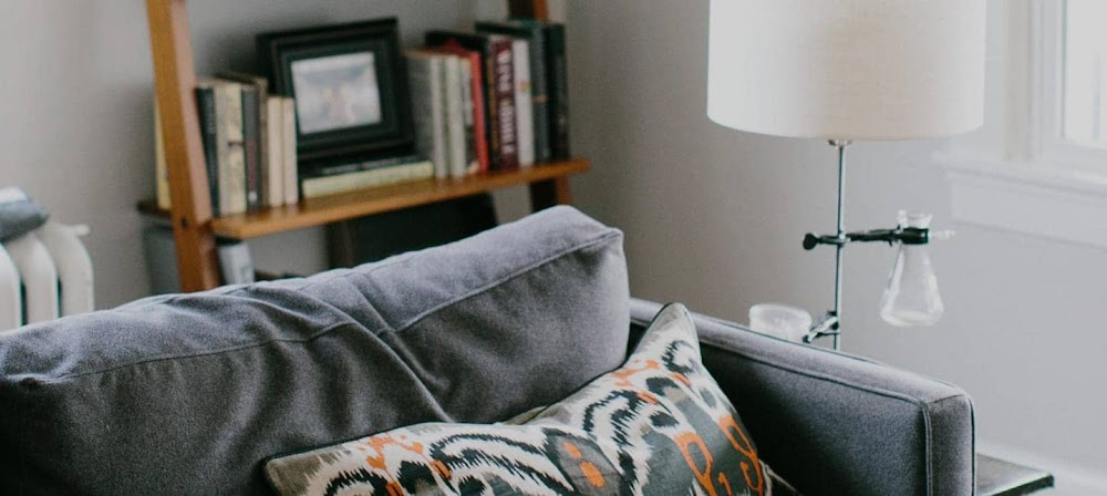 Close up photograph of a grey sofa in a living room with a lamp and wooden bookshelves.