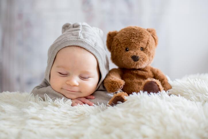 クマのぬいぐるみの横で眠っている帽子を被った赤ちゃん