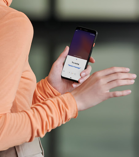A close-up image of a woman's hand holding a Google Pixel phone, showing Google Assistant being used on the screen.