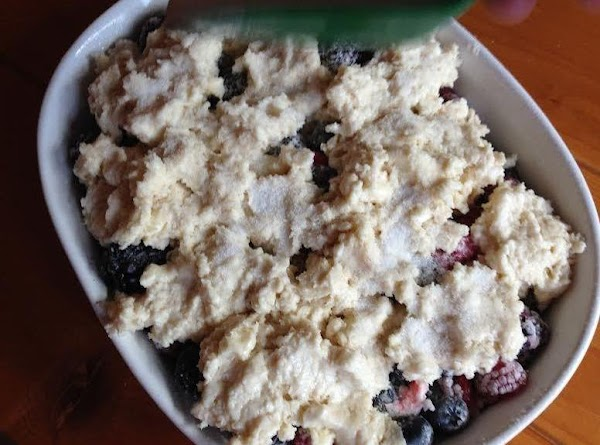 Drop topping onto berries to cover and sprinkle with sugar. Place baking dish on...
