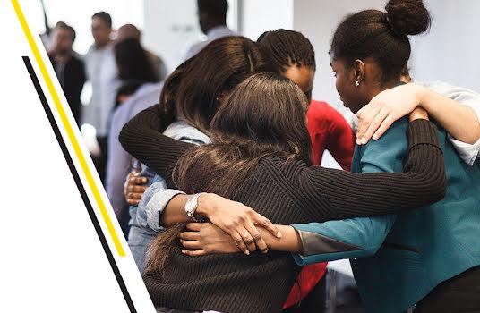 Des jeunes femmes se regroupent en se passant les bras autour des épaules.