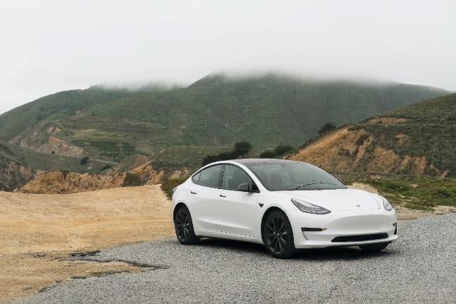 A white car on a road  Description automatically generated with low confidence