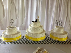 Photo: 3-tier wedding cake w/two 2-tier sides cakes. Decor: smooth whipped cream frosting w/4-dot clusters around sides, yellow ribbon wrap on bottoms & initial toppers.
