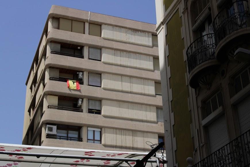 Bandera de España con lazo negro en balcón del Paseo de Almería.
