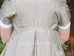 Photo: Vestido Império em cambraia branca com calda a mangas curtas e capa em tafetá bege acinzentado com acabamento em renda guipure vinho. A partir de R$ 450,00.