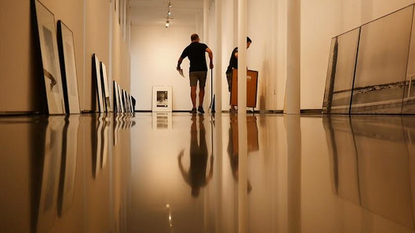 Operarios montan una exposición en el Centro Andaluz de Fotografía.