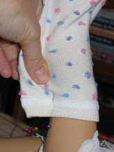 Photo: Very carefully, put a pin in the sock to hold the layers together. (Be careful so you don't scratch your doll.)  Continue pinching and pinning all the way to her foot.