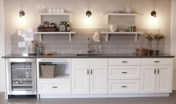 white cabinets and mini wine fridge in a small wall bar space